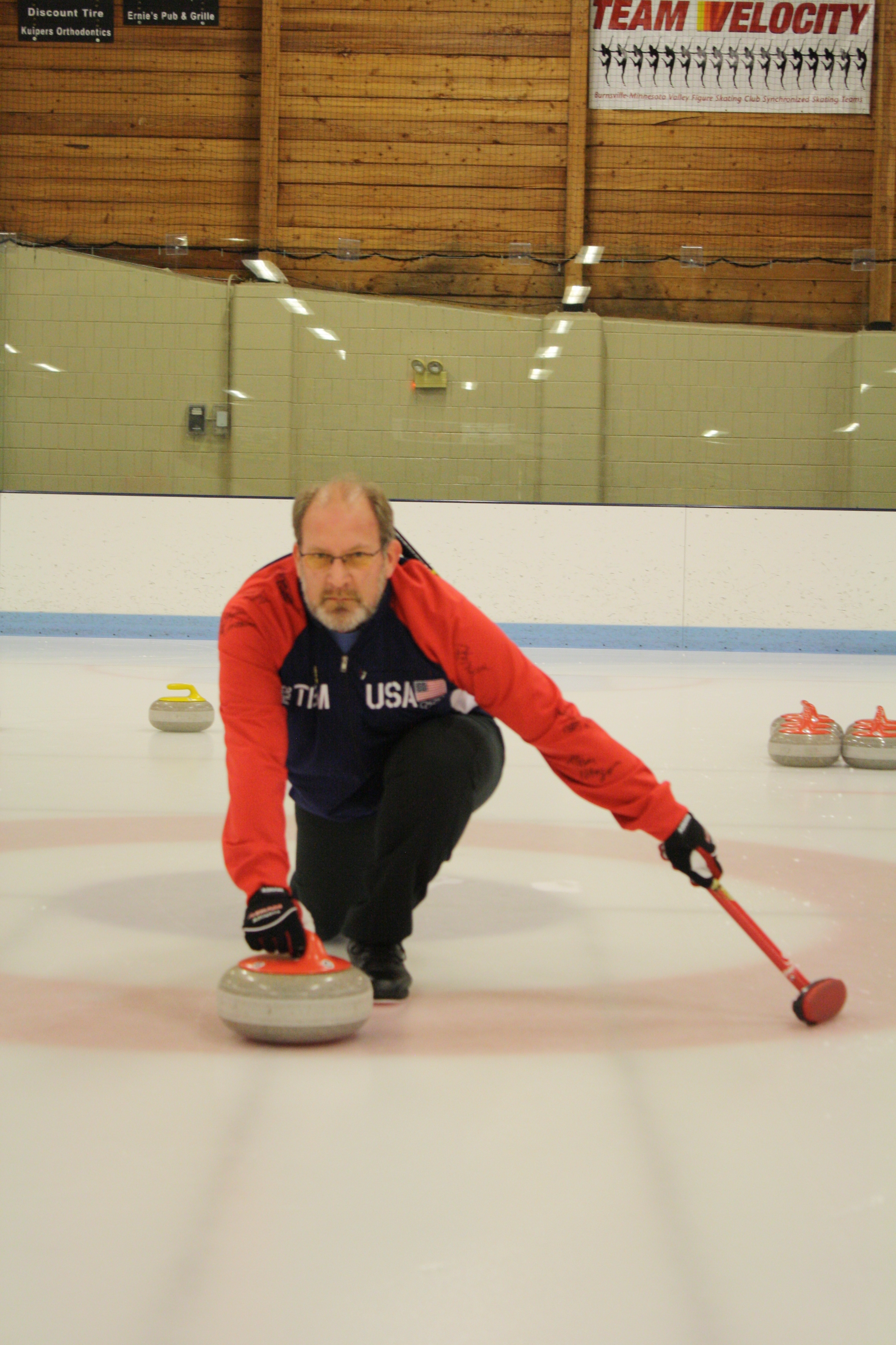 Man pushing a curling stone