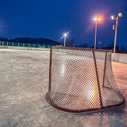 Outdoor ice rink and broomball net at night.
