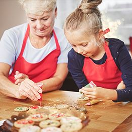 Grandmother and young girl decorating Christmas cookies