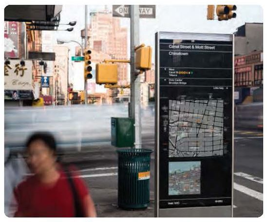 People walk past a large kiosk that displays an area map and neighborhood names