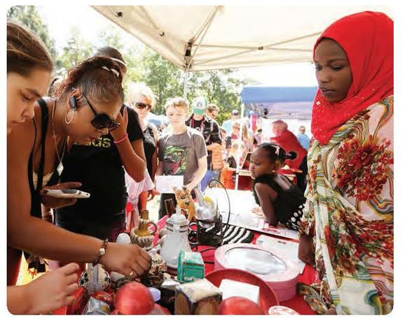 People of various ethnicity shop at a vendor booth staffed by a Somali woman