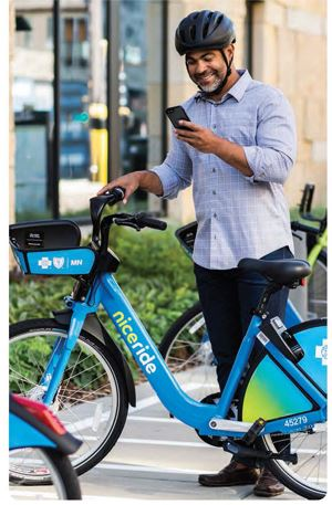 A man looks at his cell phone while standing behind a Nice Ride bike provided by Blue Cross Blue Shi