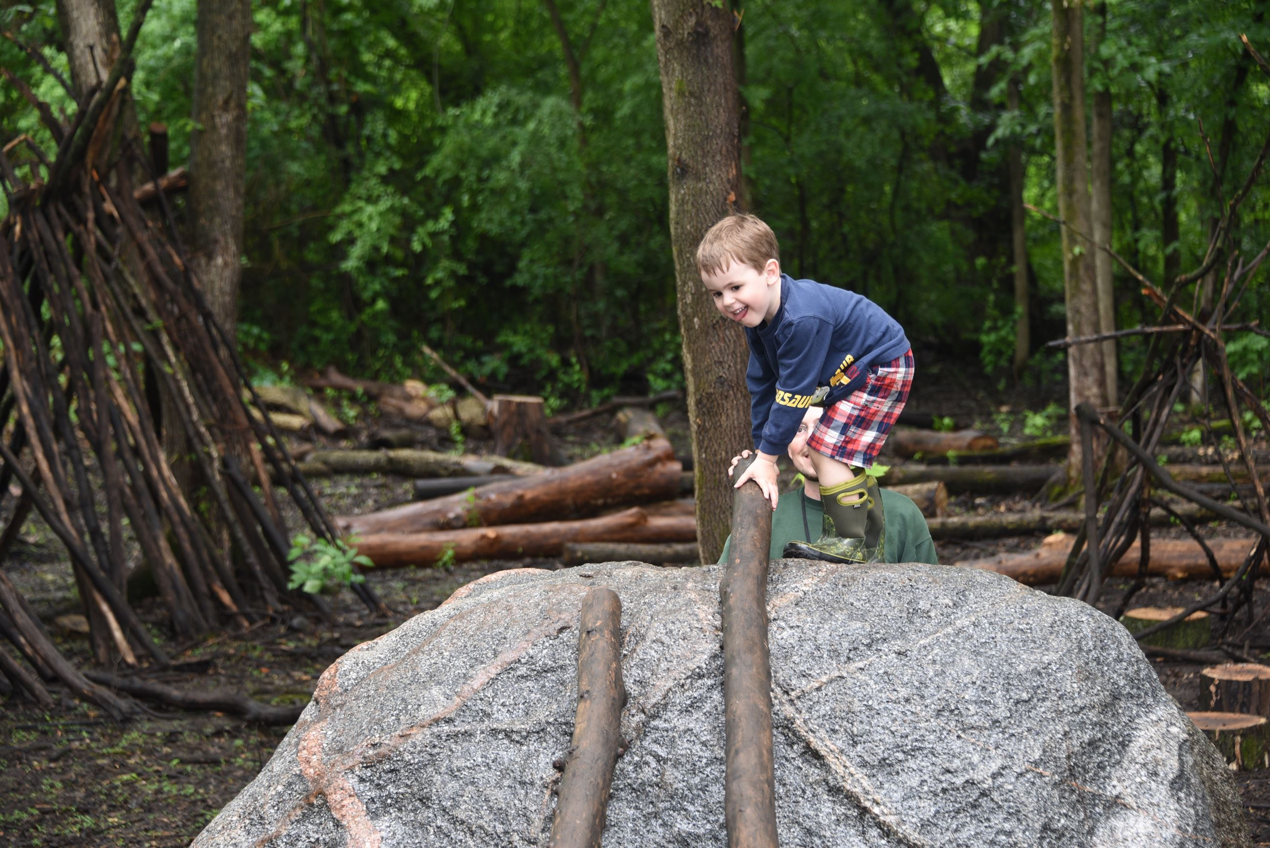 A young boy climbs on a large rock in a nature play area in Terrace Oaks Park