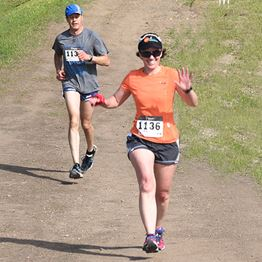 A woman and man with racing numbers on their shirts run on a dirt path