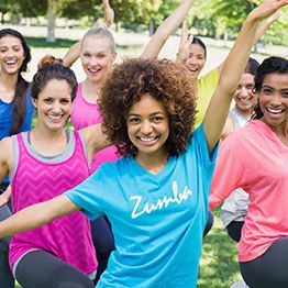 Seven women dance zumba in a park