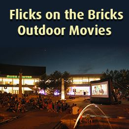 Nicollet Commons Park at night. People watch a movie on a large inflatable screen.