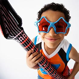 Young boy wearing star-shaped sunglasses holds an inflatable guitar