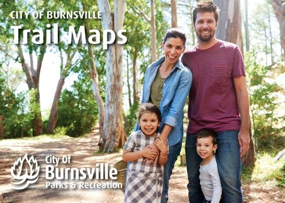 Cover of trail booklet featuring family smiling on a trail in the woods
