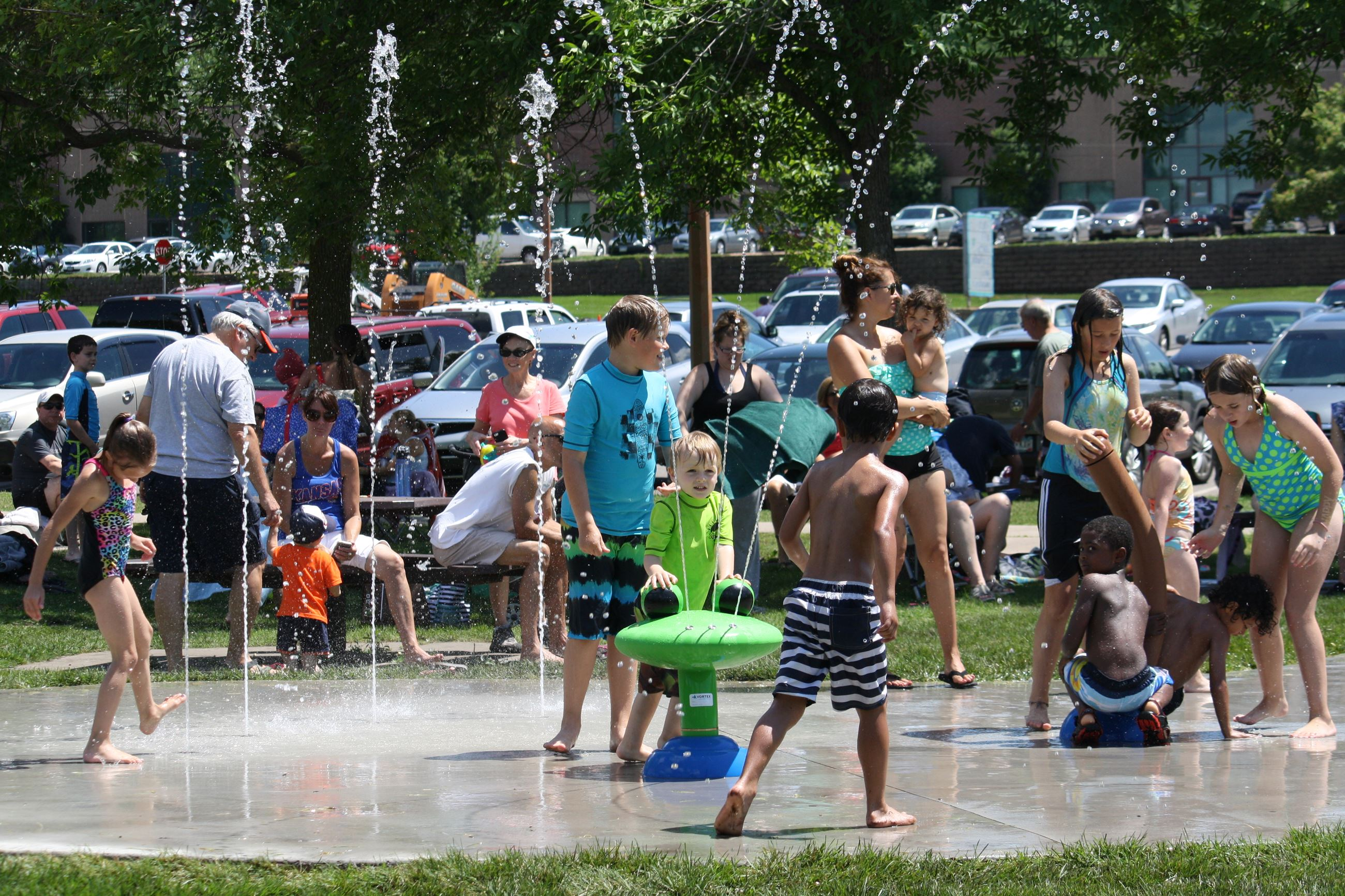 Children play in water fountains at a splash pad