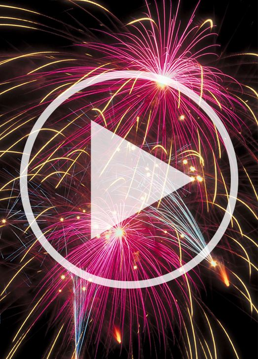 Brightly colored fireworks. Video play icon is slightly transparent over the photo