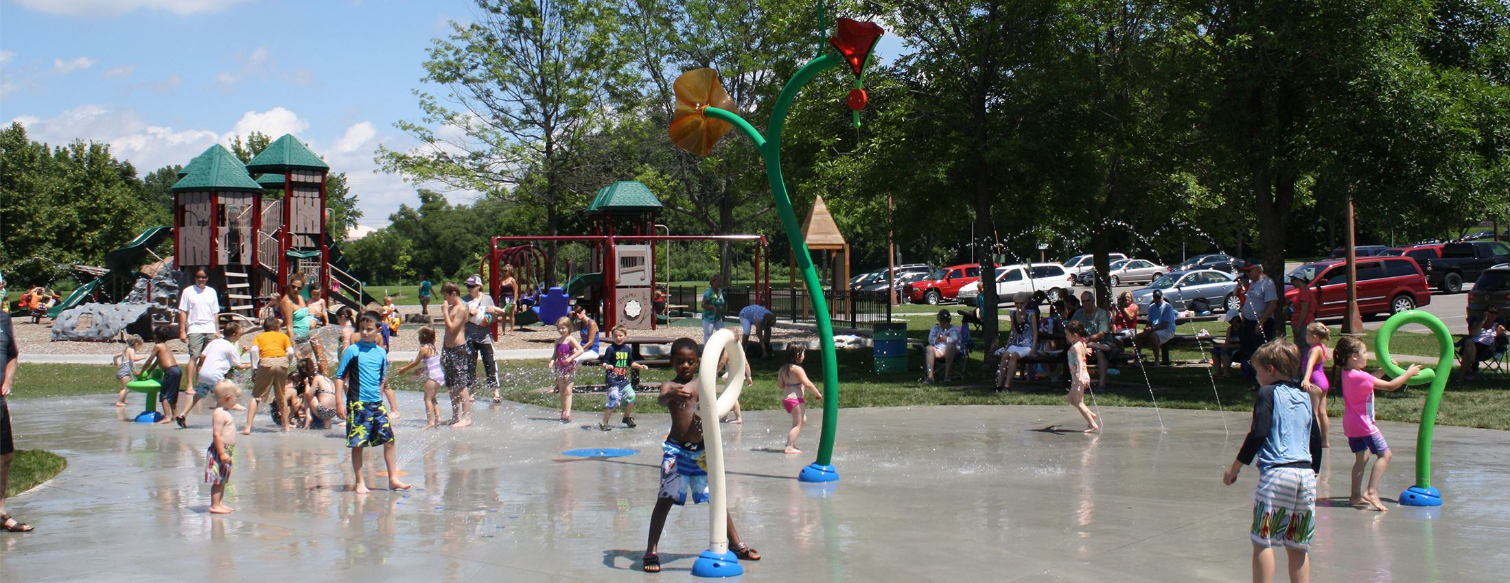 Kids play in a splash pad in front of a playground at Cliff Fen Park