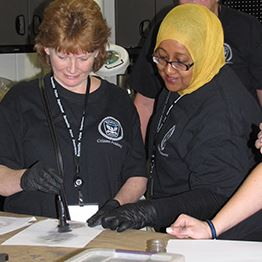 Two women practice dusting for fingerprints