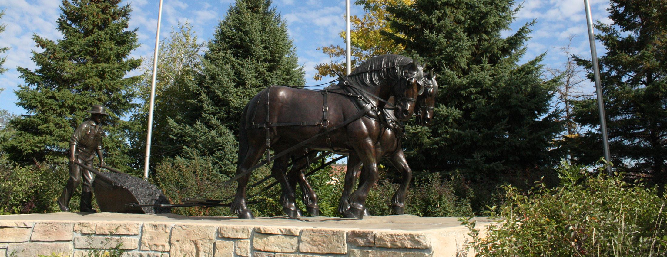 Sculpture of horses pulling and a man pushing a plow