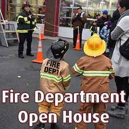 Two young kids dressed as firefighters watch a Burnsville firefighter give a demonstration
