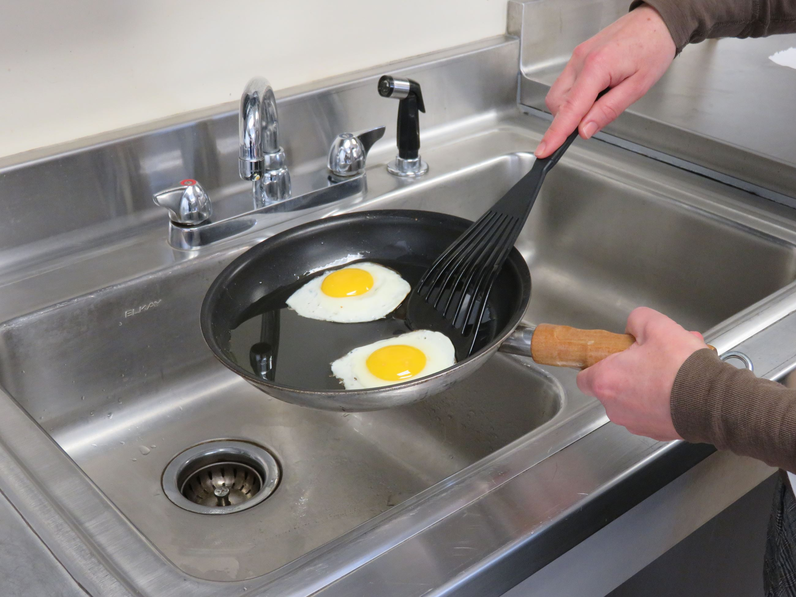 Person about to put fried eggs into the sink to dispose of them.