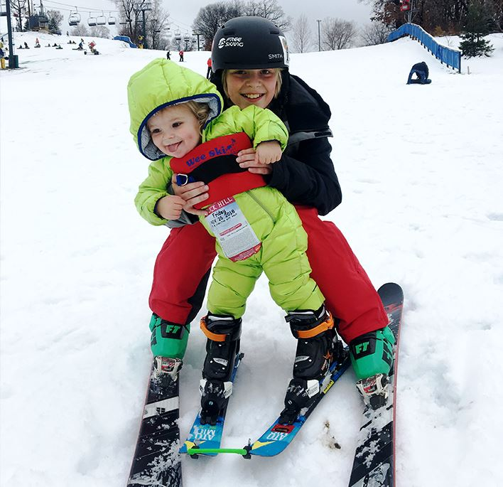 Two small children skiing in winter