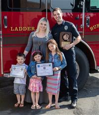 Walker with his wife and children standing in front of a Burnsville fire truck